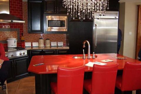 кухня с черными фасадами и столовой группой красного цвета